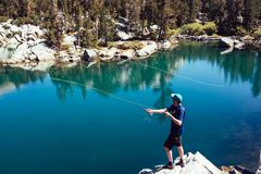Man in Blue T Shirt Fishing on Lake during Day Time Royalty Free Stock Images