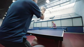 Man in blue T-shirt playing a ping-pong with woman at the court stock video