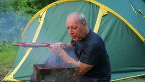 A man in a blue T-shirt is sitting in the forest on the background of a green tent, blowing on burning coals in his brazier. stock video