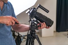 A man in a blue t-shirt tuns up a professional camera for work on the background of studio stock photo