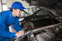 Man in blue technician uniform going to repair for car maintenance.  royalty free stock photo