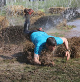 Man in blue tshirt makes a spectacular overturn in the mud Royalty Free Stock Photography