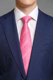 Man in blue tuxedo with pink tie stock image