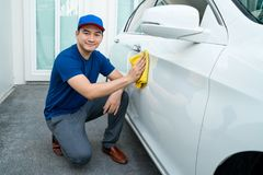 Man in blue uniform clean a white car. Car detailing, Man in blue uniform clean a white car in hand holding a microfiber washing large car Royalty Free Stock Photography