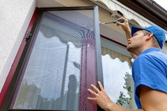 Man installing mosquito net wire screen on terrace doors royalty free stock photo