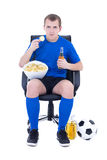 Man in blue uniform watching football with chips and beer isolat Royalty Free Stock Photo