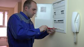 Man in blue uniform working on a circuit breaker at flat house stock footage