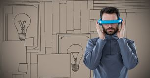 Man in blue virtual reality headset against brown hand drawn wall with pictures Stock Photos
