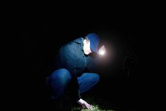 Man in blue wearing looking for something in wet grass with light in hand , scary or fairytale night. Adult man in blue wearing sit and looking for something in stock images
