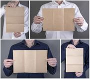 A man holding booklet. A man in a blue and white shirt holding a blank booklet royalty free stock photos