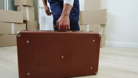 Man carries old soviet valise into room filled with boxes. Man in blue workwear carries old soviet valise with metal parts into room filled with boxes for stock video