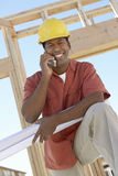 Man With Blueprints Using Cellphone At Site Royalty Free Stock Images