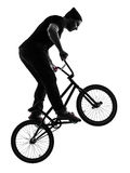 Man bmx acrobatic figure silhouette. One caucasian man exercising bmx acrobatic figure in silhouette studio isolated on white background Royalty Free Stock Photos