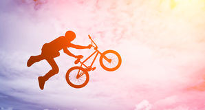 Man  with a bmx bike. Man doing an jump with a bmx bike against sunshine sky Stock Photography