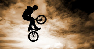 Man with a bmx bike. Silhouette of a man doing an jump with a bmx bike Stock Images