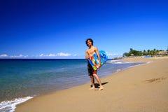 Man with board on beach of Atlantic ocean Stock Image