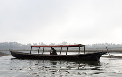 Man on Boat. A Burmese man rests on his boat in the early morning on the Irrawaddy River in Myanmar Stock Photos