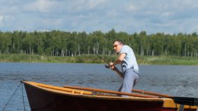 A man in a boat catches caught fish on a lake in the forest royalty free stock photo