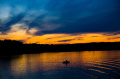 Man in boat fishing under yellow sky. Man in boat is fishing on the river Kama, Ural, Russia. Sunset. The sky seems to be drawn stock photos