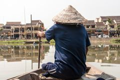 Man in Boat in Hoi An, Vietnam. A disabled man makes money by rowing tourists through the canals in Hoi An, Vietnam stock image