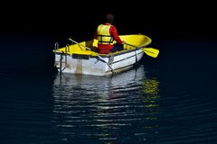 Man in boat inside cave. Man wearing life vest inside yellow wooden boat inside cave royalty free stock photography