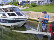 Man at Boat Launch Loading a Fishing Boat on Trailer Stock Photography