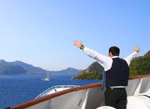 Man on the boat looking at the sea. Man with hands up too the sea Stock Photo