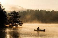 Man in a Boat on a Mountain Lake Royalty Free Stock Photography