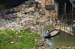 Man in a boat by a mountain of rubbish. DHAKA, BANGLADESH - NOVEMBER 9: Woman is standing on a mountain of rubbish and a man is sitting in a boat on November, 9 Royalty Free Stock Photography