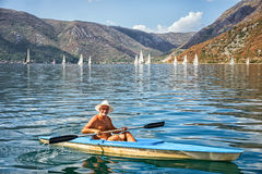 Man in a boat. Risan, Montenegro -September 3, 2017: Unknown man in a boat with paddles on the background of landscape of Kotor bay with yachts royalty free stock photos