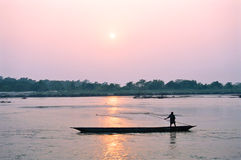 Man on boat at sunset, Chitwan Nepal. A fisherman on a boat at sunset with the sun reflecting in the water, Chitwan National Park, Nepal royalty free stock photos