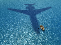 Man in a boat under a flying plane Stock Images