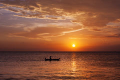 Man in boat witnessing a magical golden sunset in Bali. Indonesia royalty free stock photography