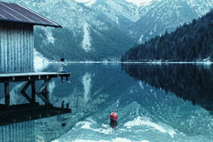 Man on boathouse on mountain lake Stock Images