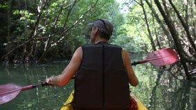 Man boating in kayak along lagoon stock video