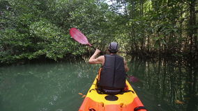 Man boating in kayak along lagoon pass cliff stock footage