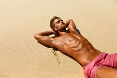 Man Body On Beach. Summer Male Lying On Sand At Resort Stock Photo