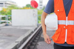Man body engineer hand holding white helmet for train. Security of the person and the background for the railroad stock illustration