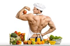 Man bodybuilder cook with apple on biceps Stock Photography