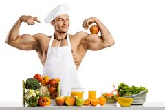 Man bodybuilder cook with apple on biceps Stock Photos
