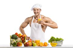 Man bodybuilder cook, cooking freshly squeezed juice and vegetab Royalty Free Stock Photos