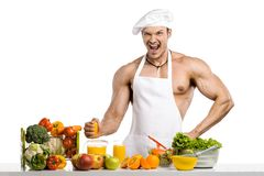 Man bodybuilder cook, cooking freshly squeezed juice and vegetab Stock Images