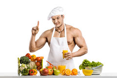 Man bodybuilder cook, cooking freshly squeezed juice and vegetab Royalty Free Stock Photo