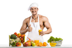 Man bodybuilder cook, cooking freshly squeezed juice and vegetab Stock Image