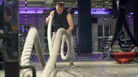 Man bodybuilder doing exercise using battle ropes. In gym. Fitness, sport, exercising, training and lifestyle concept stock video footage
