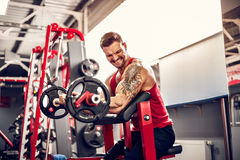 Man bodybuilder doing the set of a barbell exercise in a gym. Real time shot Royalty Free Stock Image