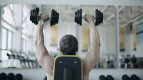 Man bodybuilder execute exercise with dumbbells in gym. Footage of back body stock video