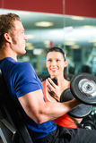 Personal Trainer in gym and dumbbell training Royalty Free Stock Photo