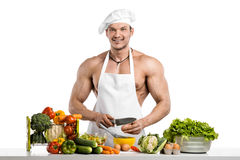 Man bodybuilder in white toque blanche and cook protective apron Royalty Free Stock Images