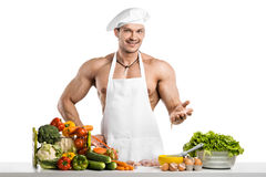 Man bodybuilder in white toque blanche and cook protective apron Stock Photos
